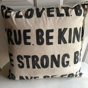 Beige throw pillow with black writing